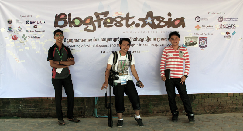 Theara, Chetra (me) and Chenda took a photo in front of the backdrop of BlogFest Asia 2012 held in Siem Reap.